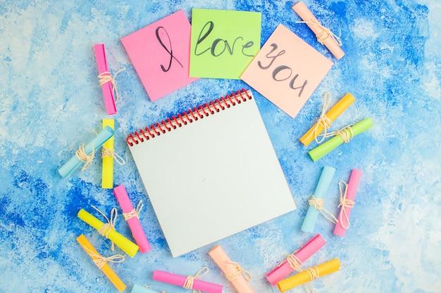 Widok z góry kocham cię napisane na karteczkach samoprzylepnych przewiń życzę papiery notatnik na niebieskim tle