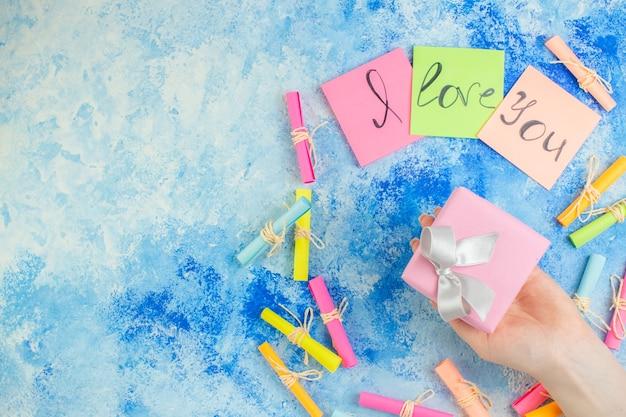 Widok z góry kocham cię napisane na karteczkach samoprzylepnych przewiń życzę papiery prezent w ludzkiej dłoni na niebieskim tle kopiuj miejsce
