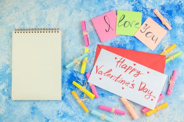 Widok z góry kocham cię napisane na karteczkach samoprzylepnych przewiń życzę papiery szczęśliwe walentynki napisane na papierowym notatniku na niebieskim tle
