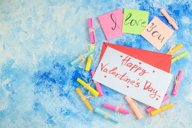 Widok z góry kocham cię napisane na karteczkach samoprzylepnych przewiń życzę papiery szczęśliwe walentynki napisane na papierze na niebieskim tle kopiuj miejsce