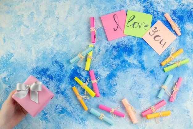 Widok z góry kocham cię napisane na karteczkach samoprzylepnych przewiń życzę sobie prezentów w ludzkiej dłoni na niebieskim tle