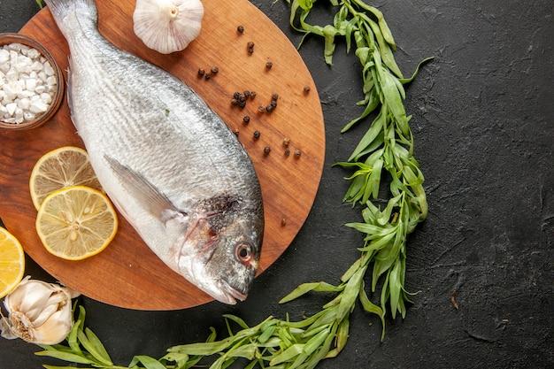 Widok z góry koło estragonu wokół świeżej surowej ryby czosnek sól morska w misce na okrągłej drewnianej desce na czarno