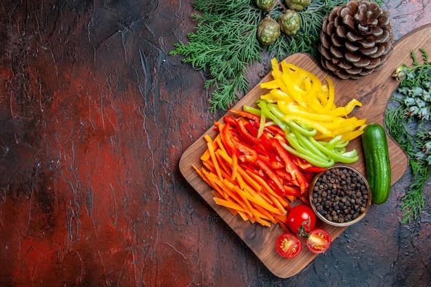 Widok z góry kolorowa papryka cięta pieprz czarny pomidory ogórek na desce do krojenia gałęzie sosny na ciemnoczerwonym stole wolne miejsce