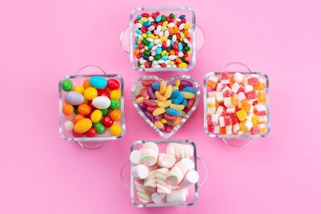Widok z góry kolorowe cukierki i pianki w okularach na różowym biurku, kolor słodkiego cukru