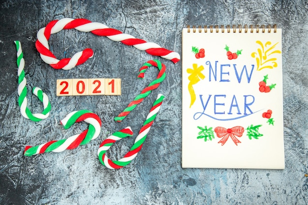 Widok z góry kolorowe cukierki świąteczne drewniany blok nowy rok napisany na notebooku na szarym tle