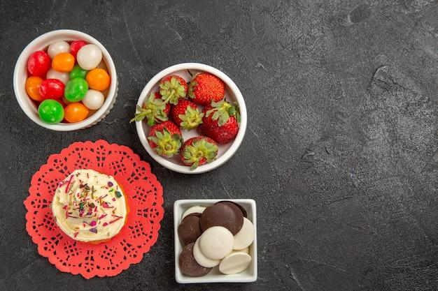 Widok z góry kolorowe cukierki z ciasteczkami i truskawkami na ciemnym tle owocowe jagody cukierkowe ciasteczka