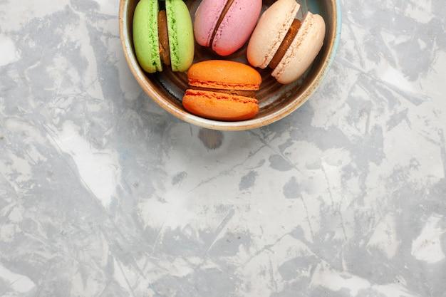 Widok z góry kolorowe francuskie macarons pyszne małe ciasta na jasnobiałej powierzchni