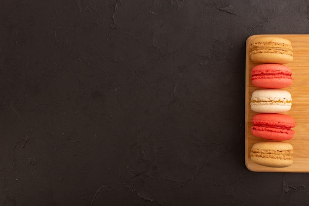 Widok z góry kolorowe francuskie makaroniki pyszne na drewnianym biurku i ciemny stół ciasto biszkoptowo-cukrowe słodkie