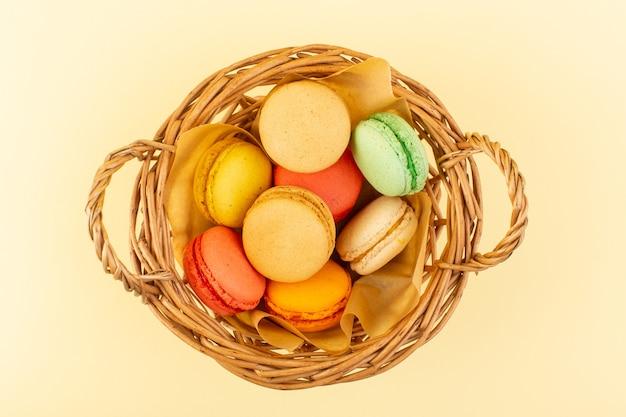 Widok z góry kolorowe francuskie makaroniki wewnątrz kosza na żółtym biurku ciasto biszkoptowo-cukrowe słodkie