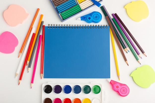 Widok z góry kolorowe kredki z farbami i naklejkami na jasnobiałej kolorowej farbie na biurko