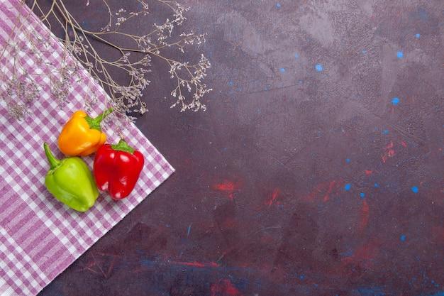 Widok z góry kolorowe papryki na szarym tle pieprz warzywny pikantne gorące jedzenie