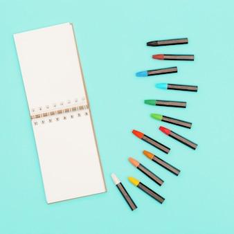Widok z góry kolorowe pastelowe kredki i notatnik na wiosnę na szkice.