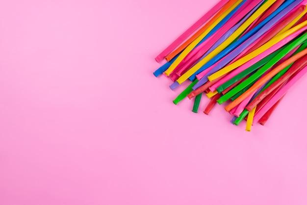 Widok z góry kolorowe patyczki długie i słomkowe wyglądające jak na różowej, kolorowej kompozycji fotograficznej