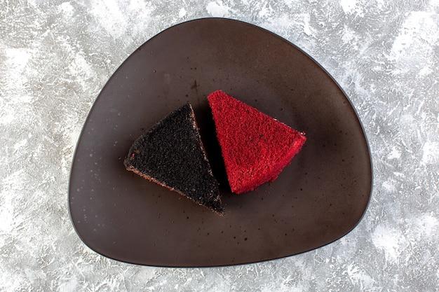 Widok z góry kolorowe plastry ciasta kawałki ciasta czekoladowego i owocowego wewnątrz brązowego talerza na szarym tle cake sweet biscuit tea