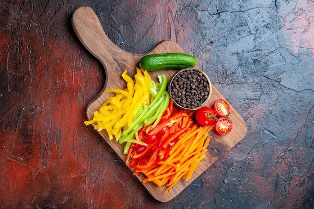 Widok z góry kolorowe pokrojone papryki czarny pieprz pomidory ogórek na desce do krojenia na ciemnoczerwonym stole z miejsca na kopię