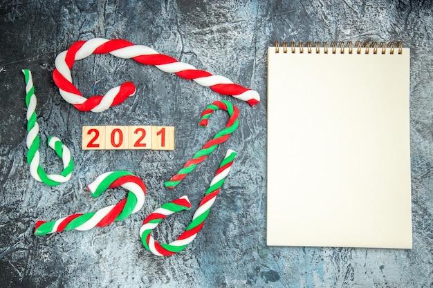 Widok z góry kolorowe świąteczne cukierki drewniany notatnik na szarym tle