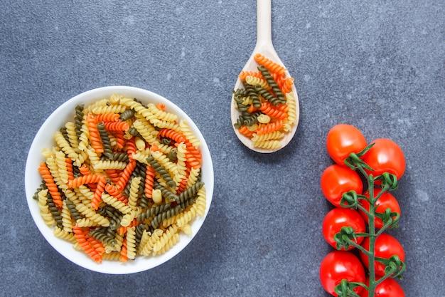 Widok z góry kolorowy makaron makaron w misce i łyżka z pomidorami na szarej powierzchni. poziomy