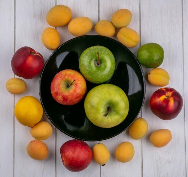Widok z góry kolorowych jabłek na czarnym talerzu z morelami i brzoskwiniami na białej powierzchni