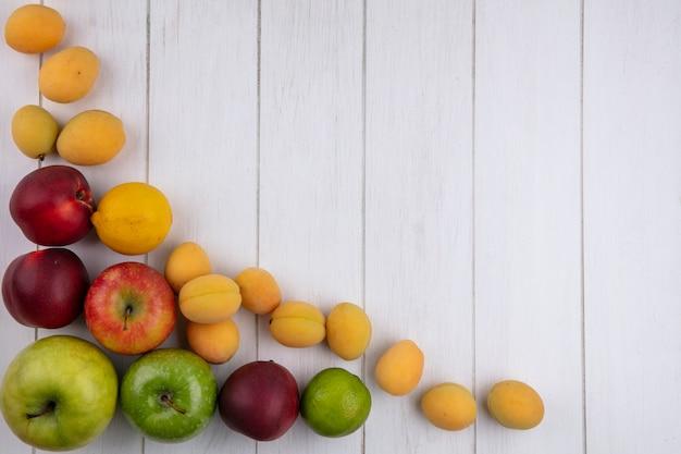 Widok z góry kolorowych jabłek z morelami i brzoskwiniami na białej powierzchni