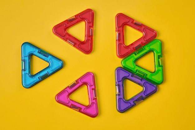 Widok z góry kolorowych magnetycznych bloków konstrukcyjnych na żółtym tle. wysokiej jakości zdjęcie