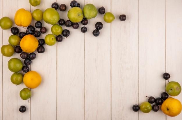 Widok z góry kolorowych świeżych owoców, takich jak żółte brzoskwinie, ciemnofioletowe tarnozielone śliwki wiśniowe na białym tle na białym drewnianym tle z miejsca na kopię