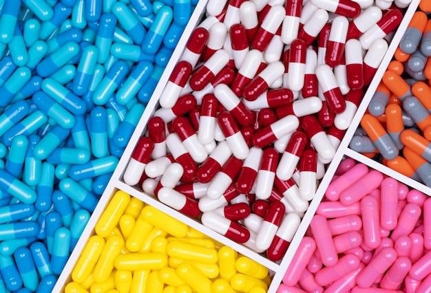 Widok z góry kolorowych tabletek kapsułkowych w plastikowej tacy. przemysł farmaceutyczny.