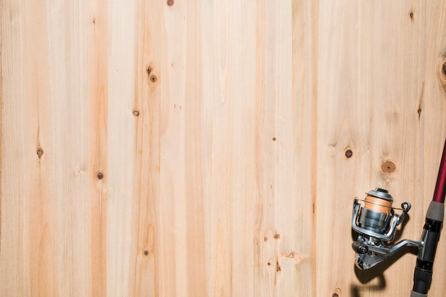 Widok z góry kołowrotka wędkarskiego na rogu powierzchni drewnianej