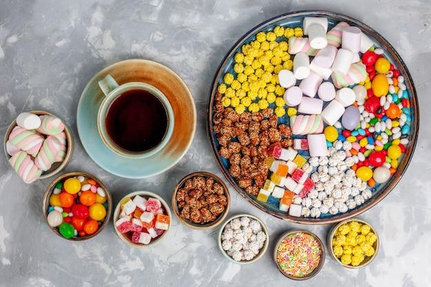 Widok z góry kompozycja cukierków różne kolorowe cukierki z ptasie mleczko i filiżankę herbaty na białym biurku cukierek cukierek bonbon słodka konfitura