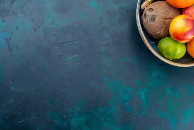 Widok z góry kompozycja owocowa mandarynki banany jabłka i kokos na ciemnoniebieskim biurku