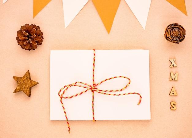 Widok z góry kompozycja świąteczna z prezentem, biały papier blank, szyszki, flagi