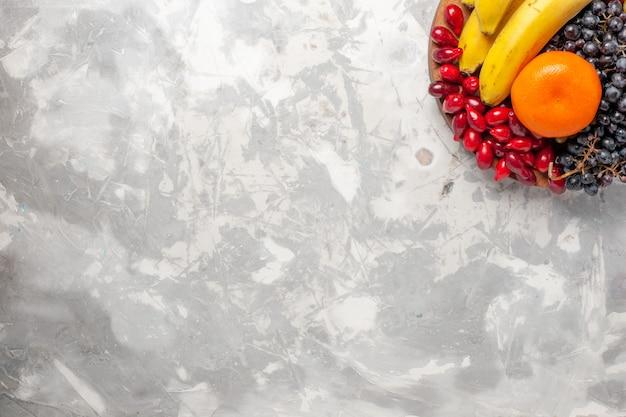 Widok z góry kompozycja świeżych owoców banany derenie i winogrona na jasnym białym tle owoce jagodowe świeżość witamina