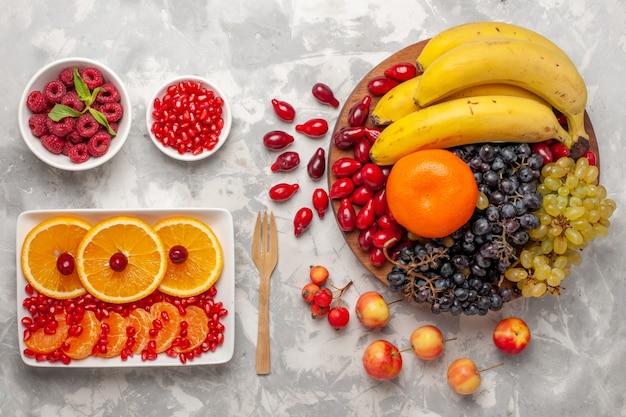 Widok z góry kompozycja świeżych owoców derenie winogrona banany i pomarańcze na białej powierzchni witamina owoców sok łagodny witamina