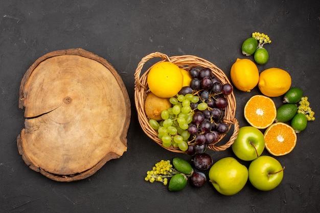 Widok z góry kompozycja świeżych owoców łagodne pokrojone i dojrzałe owoce na ciemnej powierzchni owoce świeże witaminy łagodne dojrzałe