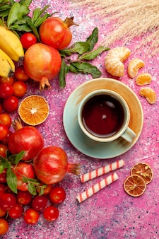 Widok z góry kompozycja świeżych owoców z filiżanką herbaty na jasnoróżowej powierzchni