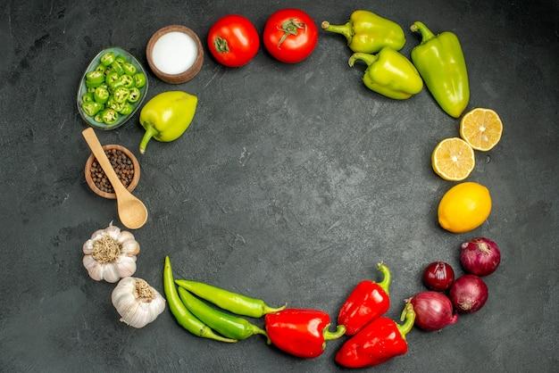 Widok z góry kompozycja warzyw pomidory papryka i czosnek na ciemnym tle