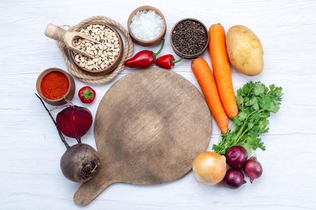 Widok z góry kompozycja warzywna ze świeżymi warzywami surowa fasola marchew i ziemniaki na białym biurku jedzenie posiłek sałatka jarzynowa