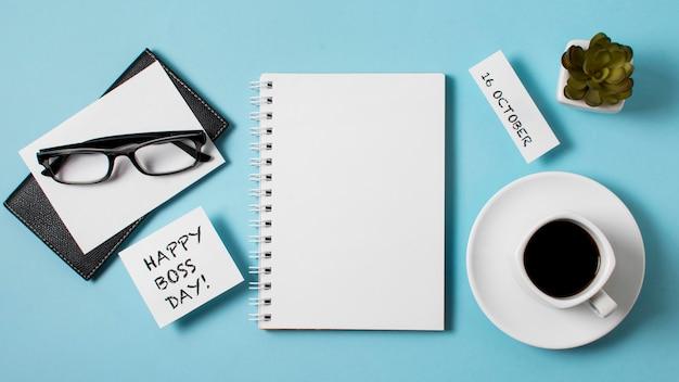 Widok z góry kompozycji dnia szefa na niebieskim tle z pustym notatnikiem