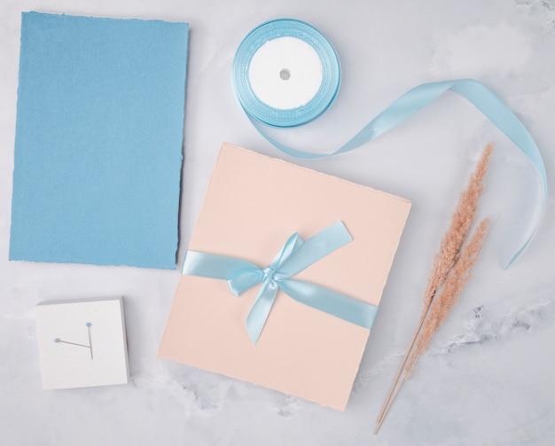 Widok z góry kompozycji ślubnej z makietą minimalistycznych zaproszeń