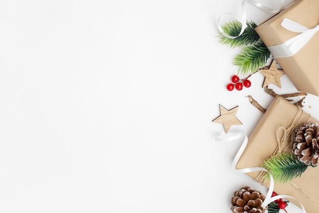 Widok z góry kompozycji świątecznej z pudełkiem, wstążką, gałęziami jodły, szyszkami, anyżem na białym stole