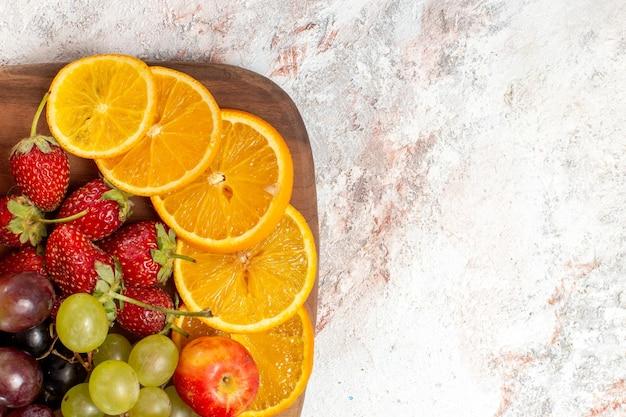 Widok z góry kompozycji świeżych owoców pomarańczy, winogron i truskawek na białej powierzchni