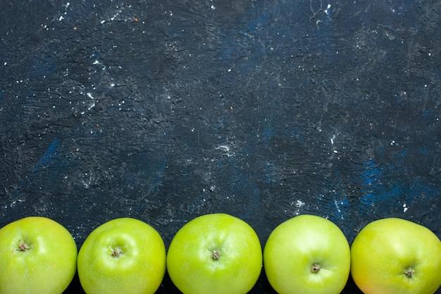 Widok z góry kompozycji świeżych zielonych jabłek wyłożonych ciemnymi, świeżymi owocami dojrzałymi