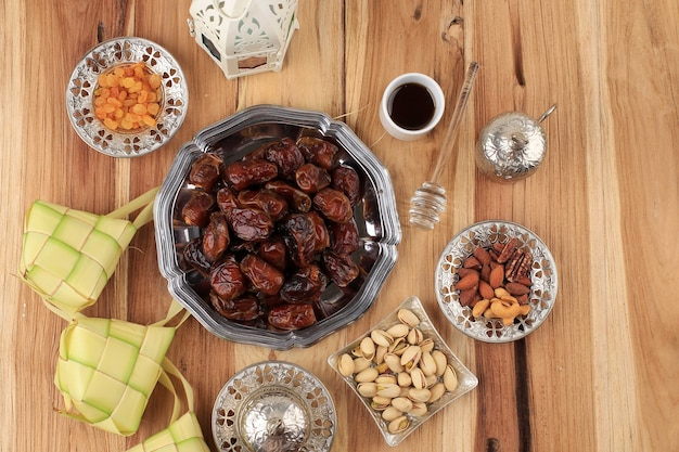 Widok z góry koncepcja jedzenie i picie ramadan z miejsca kopiowania na drewnianym stole. daktyle owoce, orzechy, nasiona, kawa, herbata, miód i ketupat. arabska żywność w stylu muzułmańskim dla ied al fitr