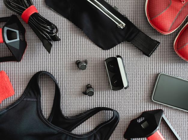 Widok z góry koncepcja odzieży sportowej z zestawem do ćwiczeń, butami do biegania, smartfonem, prawdziwymi bezprzewodowymi wkładkami dousznymi i akcesoriami do biegania sportowego na tle maty do jogi.