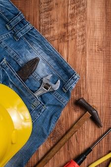 Widok z góry koncepcja projektu święto pracy z narzędziami pracy i dżinsy na tle drewniany stół.