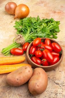 Widok z góry koncepcja składników do gotowania z pomidorami roma, ziemniakami, cebulą, marchewką i pęczkiem pietruszki na sałatkę na drewnianym tle