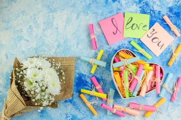 Widok z góry koncepcja walentynki kocham cię napisane na karteczkach samoprzylepnych przewiń papiery życzeń w kształcie serca bukiet kwiatów na niebieskim tle