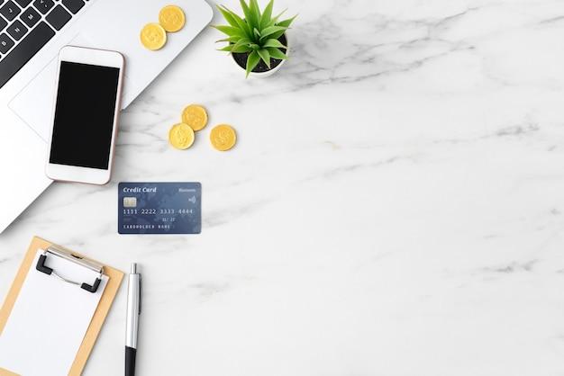 Widok z góry koncepcji planu finansowego z karty kredytowej, laptopa, uwaga na tle biały stół biurowy.