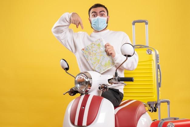 Widok z góry koncepcji podróży z młodym facetem w masce medycznej stojącej w pobliżu motocykla z żółtą walizką