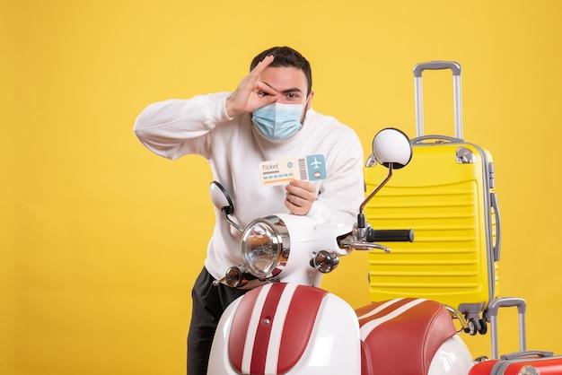 Widok z góry koncepcji podróży z pewnym siebie facetem w masce medycznej stojącej w pobliżu motocykla z żółtą walizką na nim i trzymającym bilet