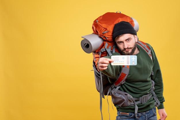 Widok z góry koncepcji podróży z pewnym siebie młodym facetem z packpack i pokazującym bilet